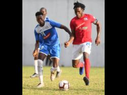 File Dunbeholden's Shaquille Dyer pulls away from Portmore United's Shai Smith in a Red Stripe Premier League mathc on December 1, 2019.