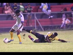 Waterhouse's Kenroy Howell slips away from Jerome Odilon of Don Bosco in a Concacaf club football match earlier this year.