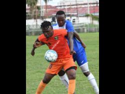 FILE Tivoli Gardens' Jermaine Johnson shields the ball from Portmore United's Ryan Wellington during a Premier League match on October 6, 2019.