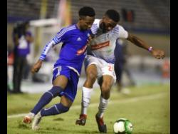 Mount Pleasant's Cardel Benbow (left) and Emelio Rousseau of Portmore United in a tussle for  the ball in a semi-final of the National Premier League on April 15, 2019.