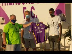 Treasure Beach FC President David Folb (left) and board member Brian Miller present new signing Romario Smith with his Treasure Beach FC jersey.