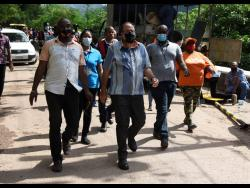 Leader of the Opposition, Mark Golding (centre), in Gordon Town where he viewed the effects of land slippage in Stand Up Hill. Golding toured sections of St Andrew that have been severely impacted by heavy rains.