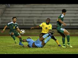 Jamaica's Javon East (second right) takes on Guyana's Samuel Cox (left), Quillan Roberts (second left) and Terrence Vancooten during a Concacaf Nations League match at the Montego Bay Sports Complex on Monday, November 18, 2019.