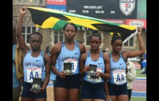 Edwin Allen's 4x100m relay team (from left) of Serena Cole (left), Kevona Davis (second left), Tina Clayton (second right) and Tia Clayton, receive their award for their victory in a record time of 43.62 seconds at the Penn Relays at the Franklin Field in Philadelphia, Pennsylvania on April 26, 2019.