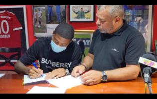 Reggae Boy Leon Bailey (left) made his move to the English Premier League Club official yesterday when he signed a contract with Aston Villa Football Club. The signing took place at  the Phoenix Academy headquarters in Kingston. Looking on is his father and agent Craig Butler.