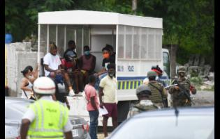 Persons being taken into custody by members of the security forces during an operation along the Hellshire main road last October. The persons were deemed to be in breach of curfew orders made under the Disaster Risk Management Act.