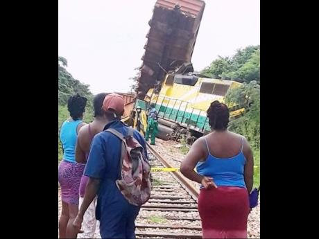 Curious onlookers view the derailed train. The driver is reportedly okay after the crash.