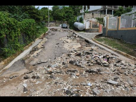 The entrance to the Bayshore Park community in the vicinity of Harbour View has been impassable since Sunday, when persistent rains undermined sections of the roadway, forcing residents to walk or use the much longer route, which is also in poor condition.