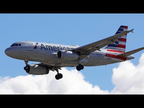 A photo of an American Airline plane in the skies.